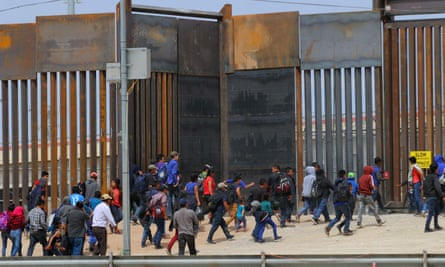 People approach a border post between the US and Mexico