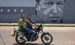 Two women ride past a mural with an image of late Venezuelan president Hugo Chavez in Sabaneta, Barinas State, Venezuela.