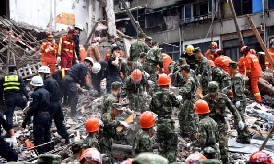 Rescuers searching for survivors on the site of collapsed residential buildings in Wenzhou.