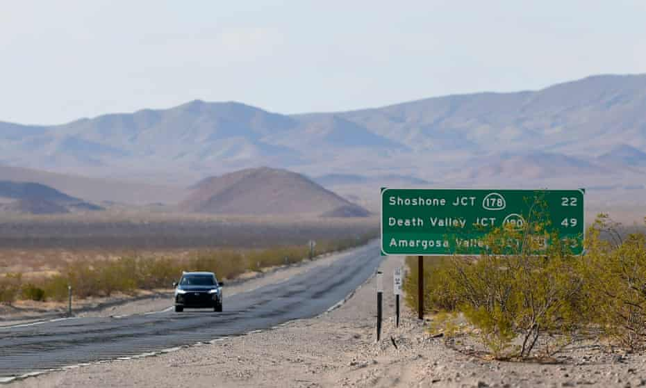 A vehicle drives through Death Valley, California, where temperatures hit 120F earlier in July. Scientists have said the barrage of heatwaves over the past month are being fueled by climate change.