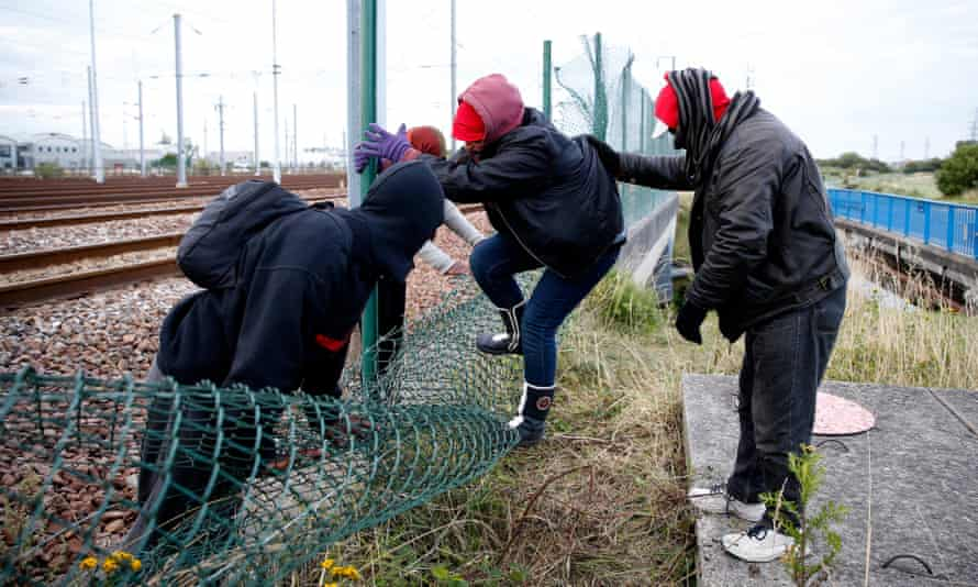 Migrants step over the fence onto the train tracks at the Eurotunnel terminal in Calais-Frethun