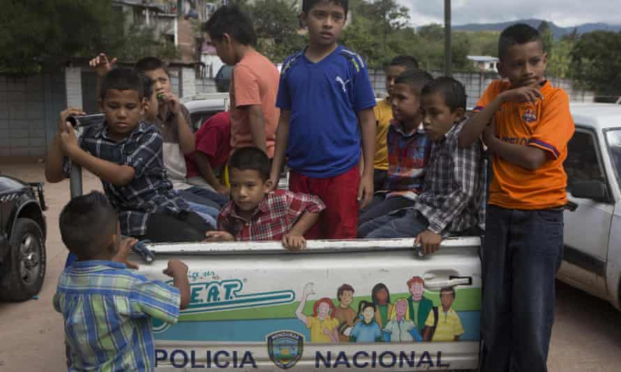 A group of Honduran children in Tegucigalpa climb into the back of a pick-up truck belonging to the National Police