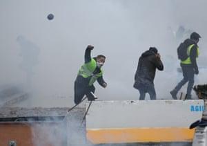A protestor hurls a rock towards police lines.