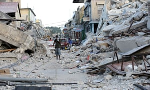 A man covers his face as he walks amid the rubble of a destroyed building in Port-au-Prince, following the devastating earthquake that rocked Haiti.