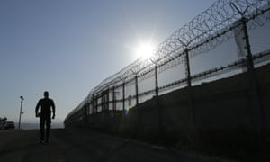 A Border Patrol agent walks along a border structure in San Diego.