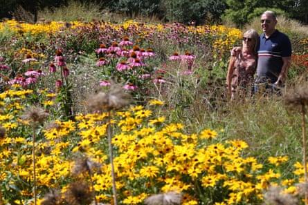 Visitors walk past flowering beds along the Broad Walk, Kew Gardens, London.