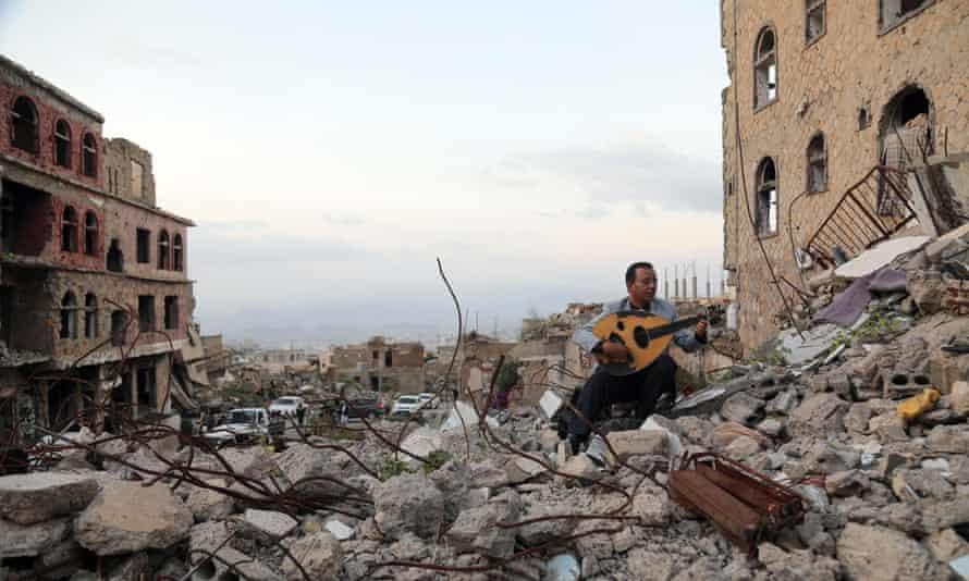 Yemeni artist sits atop the rubble