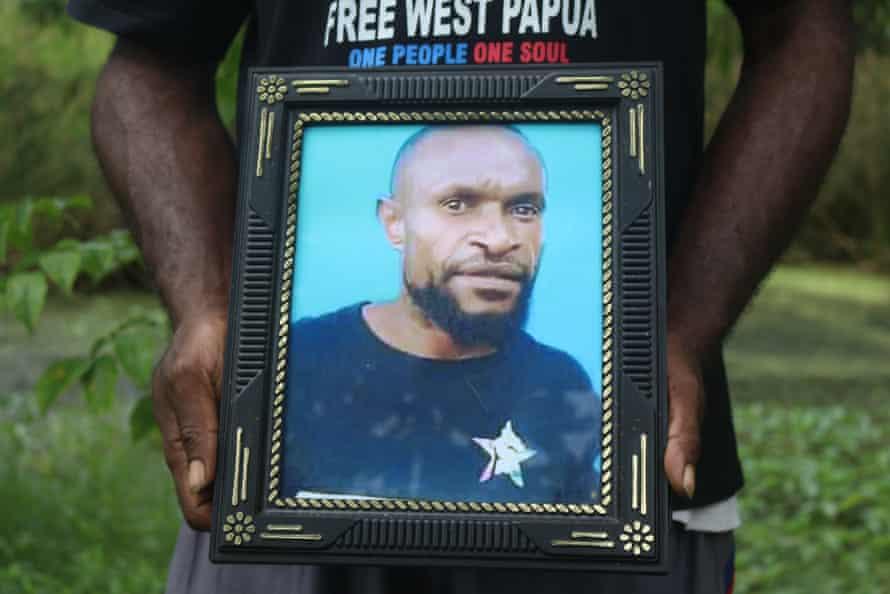 Charles Sraun holding photo of Kristian Yandun in Merauke, West Papua.