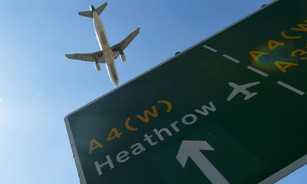 A plane passes a sign as it comes in to land at Heathrow airport.