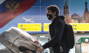 A man wearing a face mask to protect against coronavirus waits in line to check-in at Sheremetyevo international airport, outside Moscow, Russia, Saturday, Aug. 1, 2020