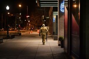 A lone National Guardsman walks down the sidewalk the night before the inauguration