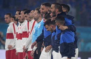 The Italian players sing their national anthem with gusto.