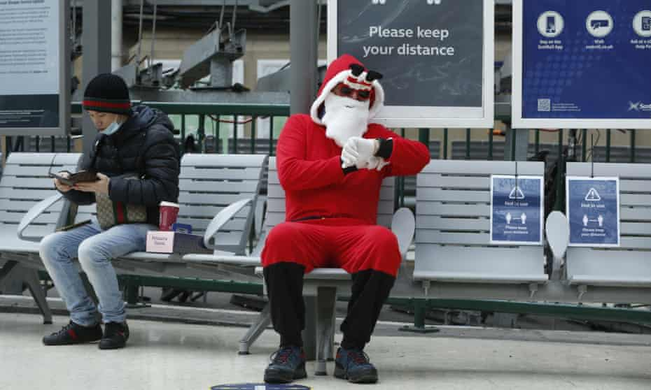 A man dressed as Santa Claus at Glasgow Central station. Restirctions on Christmas gatherings will vary across the UK.