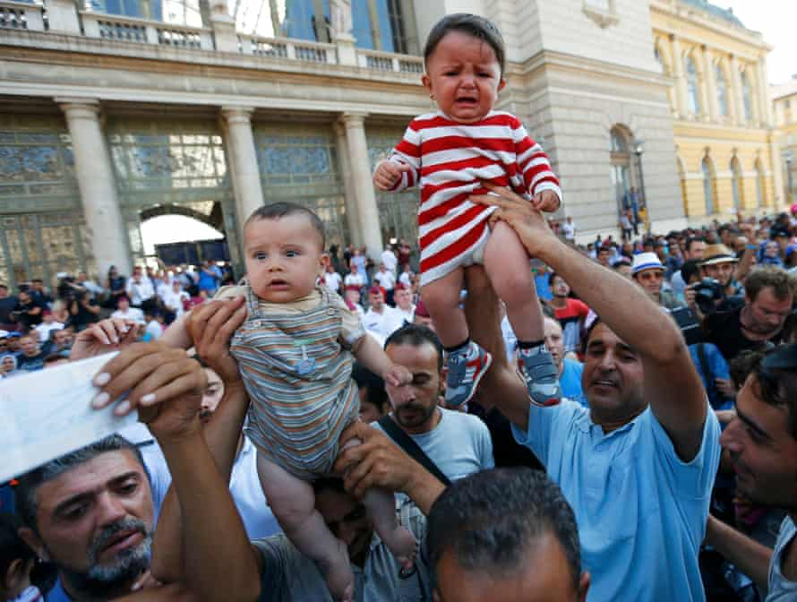 People wave their train tickets and lift up children outside the main Eastern Railway station in Budapest.