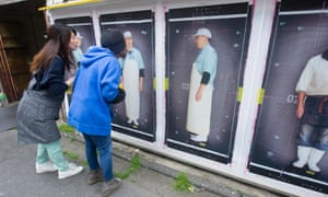 Visitors look at photographs by the French artist K-Narf in Kyoto, Japan