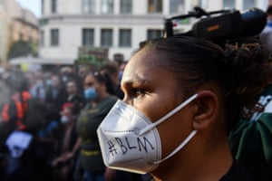 A protester watches on with the afternoon light hitting her face.