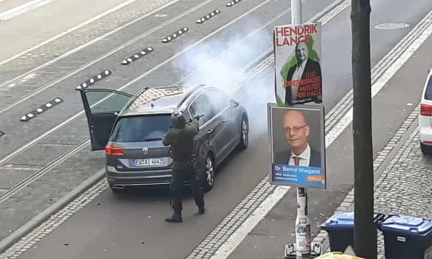A screengrab of mobile phone footage showing a man firing shots from behind a car in Halle.