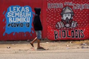 Tangerang, Indonesia A man wearing a face mask passes Covid-19 murals