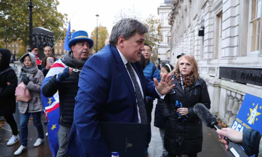 Home Office minister Kit Malthouse arrives for meeting in London surrounded by protesters.