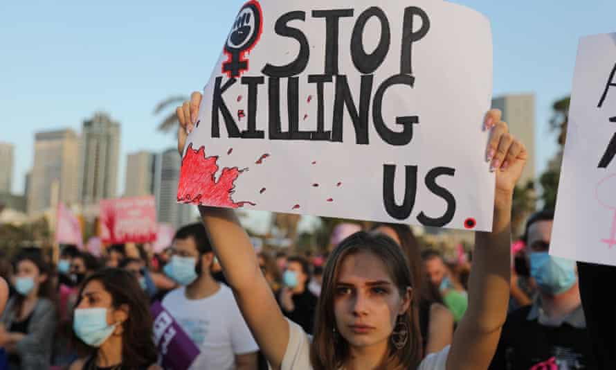 A woman holds a sign at a protest march against violence toward women in Tel Aviv in June 2020.