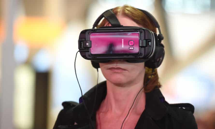 A woman uses a Samsung Gear VR virtual reality headset.
