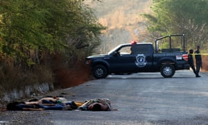 Police officers and forensic personnel work at the place where six corpses were found on a road in Mochitlan, Guerrero State, Mexico.