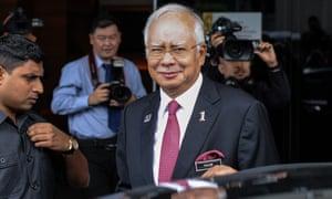 Najib Razak, smiling, with photographers in background