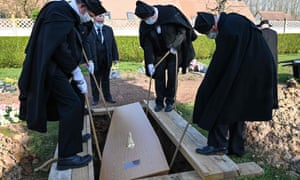 A coffin is put into a grave, at Pierrette cemetery in Bethune.