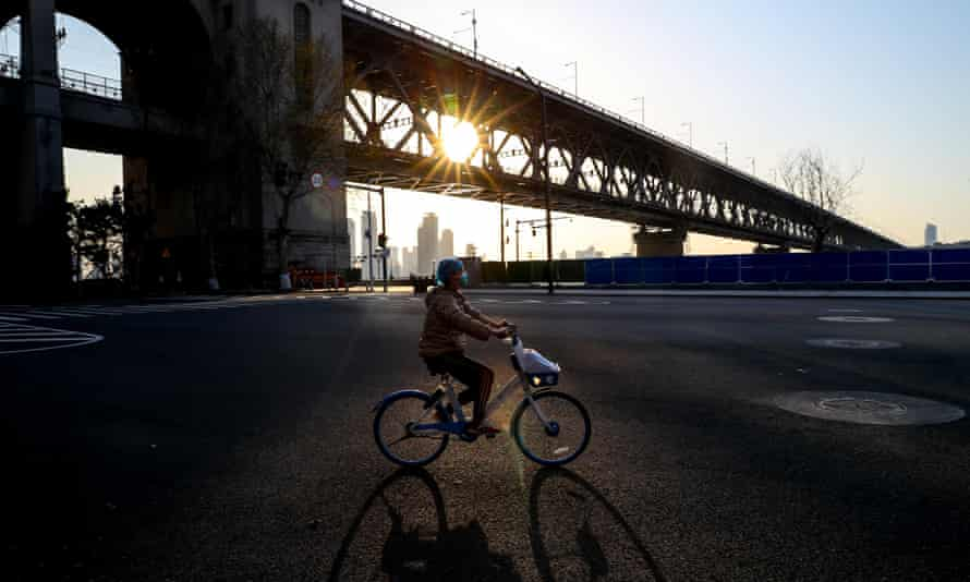 A women rides a bicycle past the Wuhan Yangtze River Bridge at sunset amid the coronavirus outbreak
