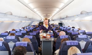 A Monarch Airlines flight attendant serving snacks to passengers.