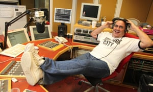 Danny Baker in a studio at the BBC's Marylebone offices, London, headphones on and his feet up on a large desk with multiple computer screens