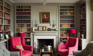 The sitting room with high ceiling, floor-to-ceiling book shelves, and red armchairs either side of an early American-style fireplace