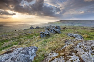 Duck's Pool Dartmoor National Park, Hayne Down, Sunrise over hilly landscape with mossy rocks in foreground
