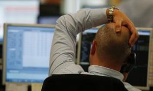 A trader looks at screens