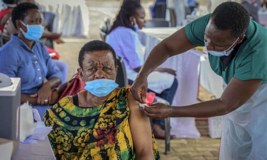 A woman receives a coronavirus vaccination at the Kololo airstrip in Kampala, Uganda.
