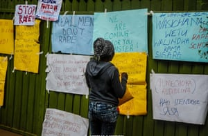 A young woman stands at a school gate with placards, which were put up by female activists protesting against gender violence, after three girls were allegedly raped at a high school in Kibera in July 2018.