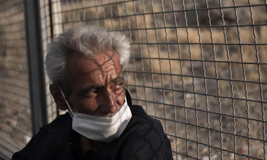 A homeless man wearing a face mask sits in an outdoor shelter in Tehran amid the coronavirus outbreak