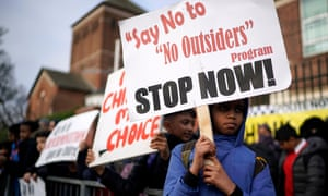 Child holds banner saying 'Say no to no outsiders'