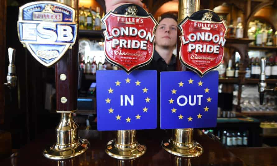 Bar coasters are pinned to ale taps at a pub in Westminster, London.