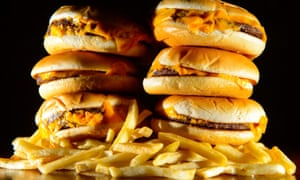 """a pile of cheeseburgers and french fries, as advertising unhealthy foods during family TV shows should be banned, MPs have said, as they called on the Government to introduce a """"sugar tax"""" on soft drinks."""