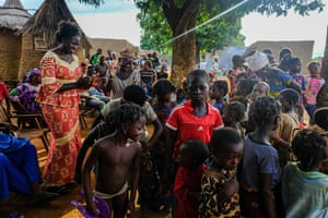 Leah Pare, head of information at Target Malaria, dances with children as they wait for a theater group to help explain the work of scientists to residents