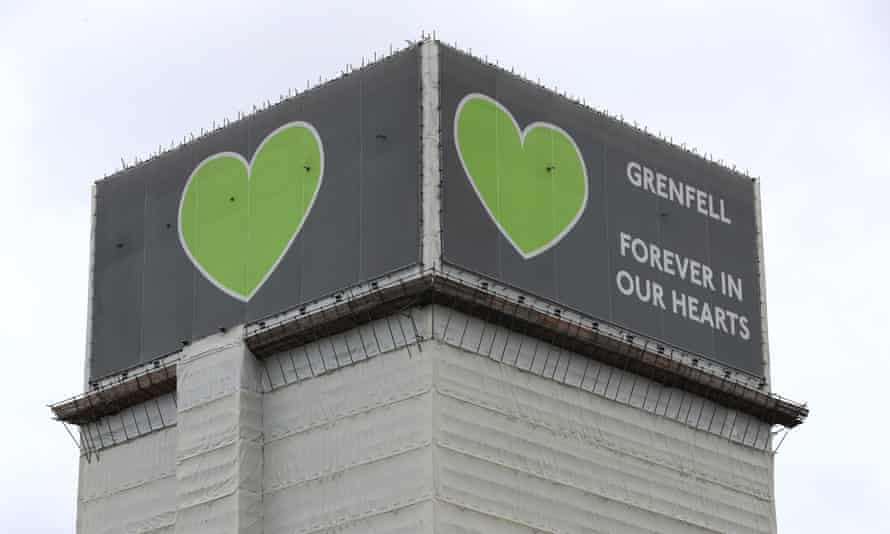 A banner at the top of Grenfell Tower that reads: 'Grenfell: forever in our hearts'