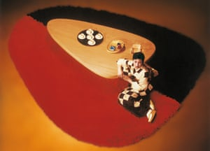 A model poses with a hinoki wood table and wool rug, circa 1955, by Charlotte Perriand.