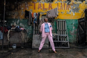 Blandine Nkouka Hombessa, 54-year-old businesswoman and sapeuse for 35 years, in Brazzaville. She wears a suit and shirt by Carucci, glasses by Ellesse, unbranded bow tie and braces and socks by Fil d'Ecosse