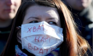 woman wears mask with cyrillic writing on it