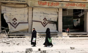 Two women walk by a building hit by an airstrike in Damascus, Syria