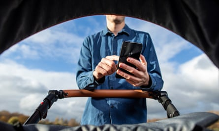 Man uses smartphone while pushing a baby's pram