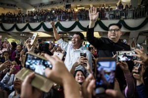 Hong Kong Impersonators of Philippine president, Rodrigo Duterte and North Korean leader, Kim Jong Un, wave as they attend a church service