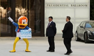 A demonstrator wearing a Donald Duck costume dances in front of the Trump International Hotel.