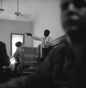 """This dramatic courtroom scene shows 64-year-old """"Uncle Mose"""" Wright, Grand-Uncle of murdered Emmett Till, 14-year-old Negro boy, as he stood up in the packed chamber and pointed a finger at defendants, Roy Bryant and John W. Milan. In answer to a question asking him to identify the man who came to his home on the night of August 28 and took young Till away with them, Wright pointed and answered, """"There they are."""" The victims mother, Mrs. Mamie Bradley, is scheduled to testify today."""
